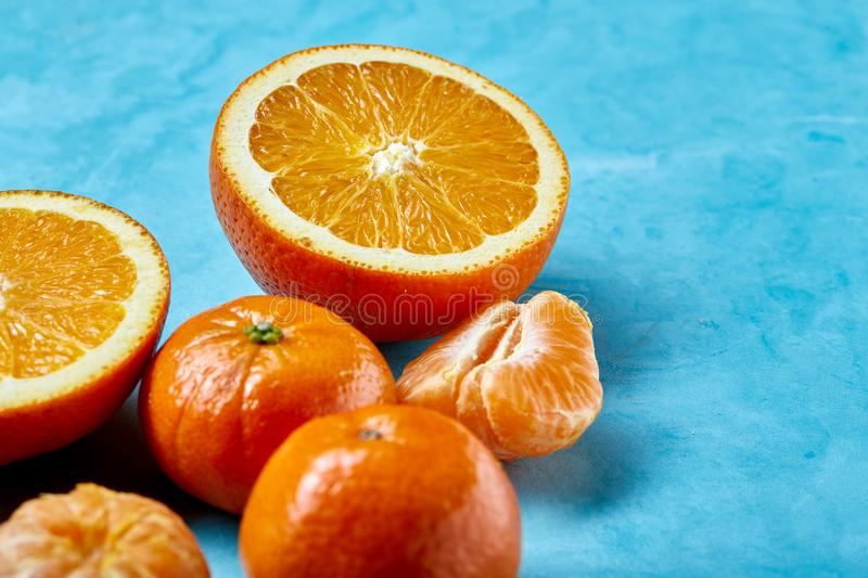 Variety of fresh citrus fruits for making juice or smoothie over blue textured background, top view, selective focus. stock photos