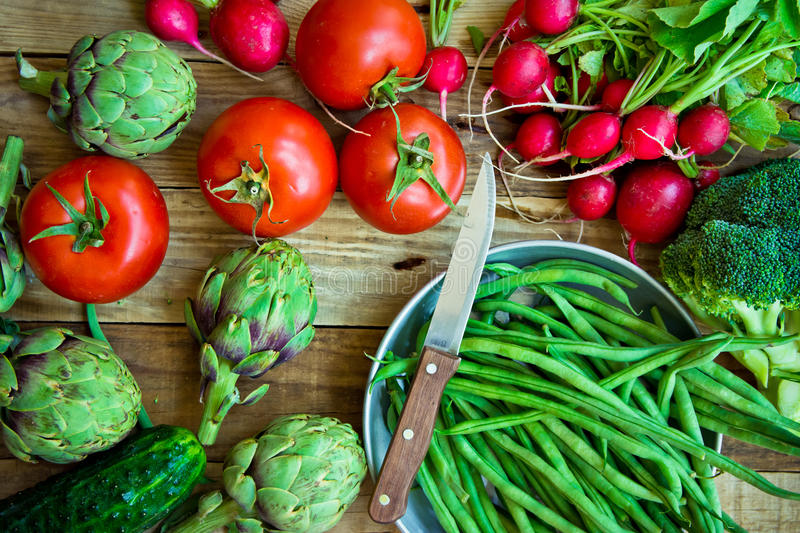 Variety of fresh colorful organic vegetables green beans, tomatoes, red radish, artichokes, cucumbers on wood kitchen table, copy royalty free stock photo