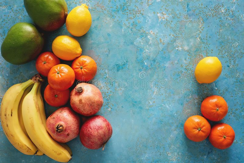 Variety of fresh fruits on rustic blue background. stock photos