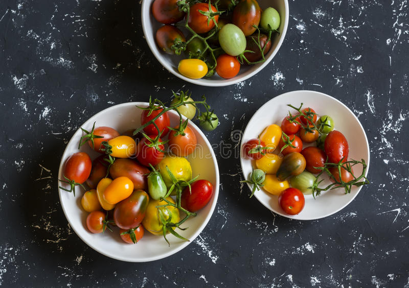 Variety fresh tomatoes on a dark background. royalty free stock photography