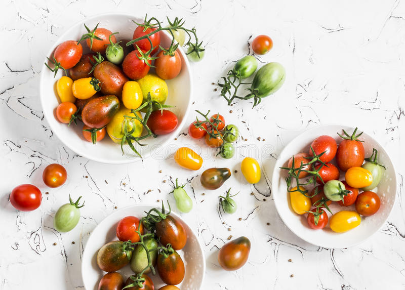 Variety fresh tomatoes on a light background. stock photography