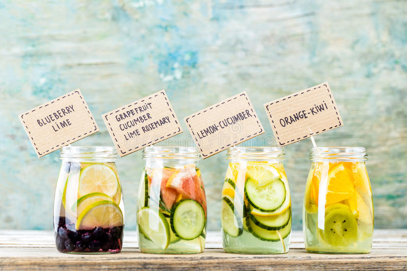 Variety of fruit infused detox water in jars royalty free stock photography