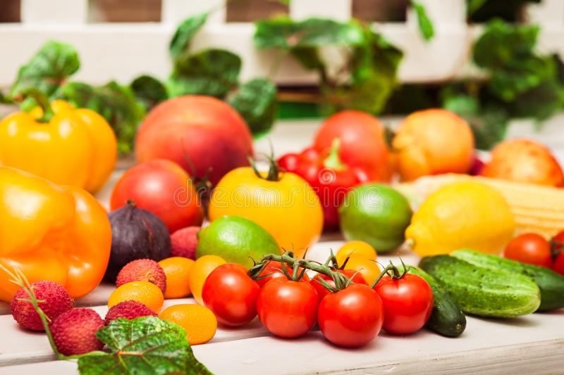Variety of fruits and vegetables scattered on the white bench en stock images