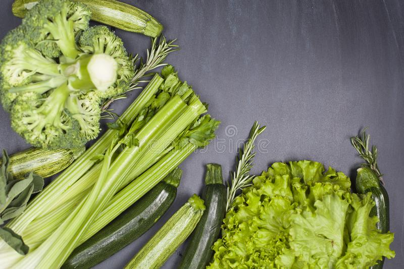 Variety of green vegetables and herbs. Clean eating food concept. On blackboard background with copy space stock images