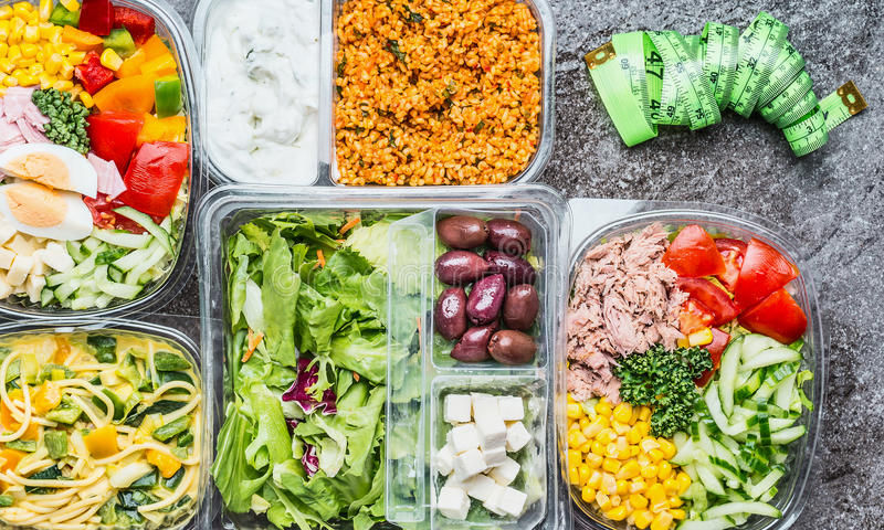 Variety of Healthy diet lunch boxes with vegetables salad and measurement tape. Salad bowls in plastic packages with measurement. Tape, top view. Dieting Take royalty free stock image