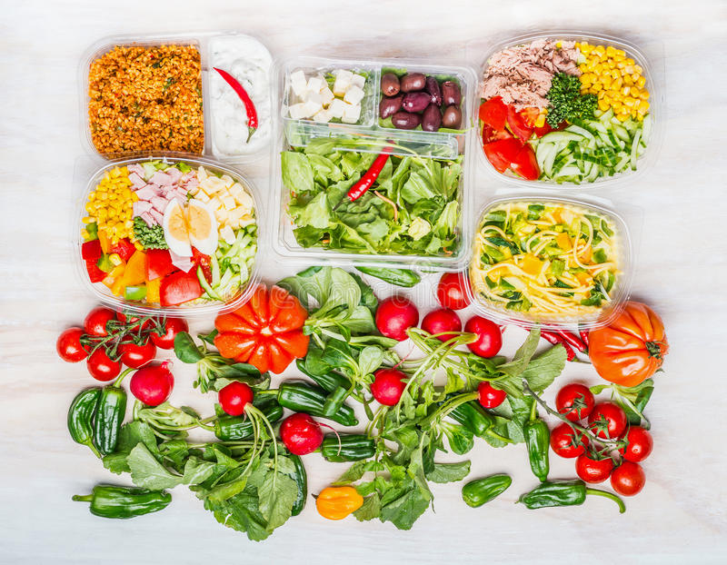 Variety of Healthy salads in lunch boxes with ingredients white wooden background stock images