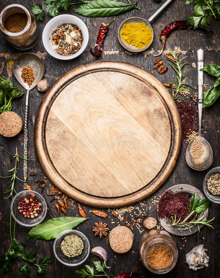 Variety of herbs and spices around empty cutting board on rustic wooden background, top view. Creative and national cuisine and cooking concept royalty free stock image
