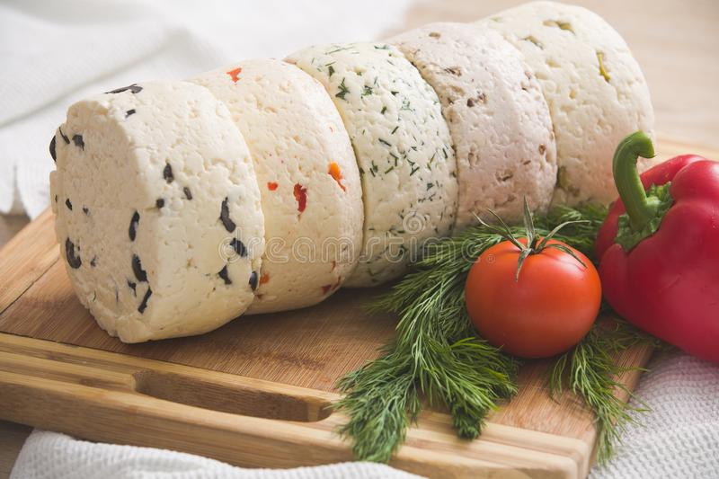 Variety of home made cheese and paprica and herbs, tomatos on a wooden board. brined curd white cheese with vegetables royalty free stock photography