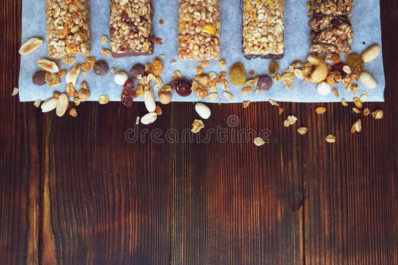 A variety of homemade granola bars, with nuts, raisins dried cherries and chocolate. Healthy granola bars with fruits, nuts and honey on wooden background. royalty free stock image