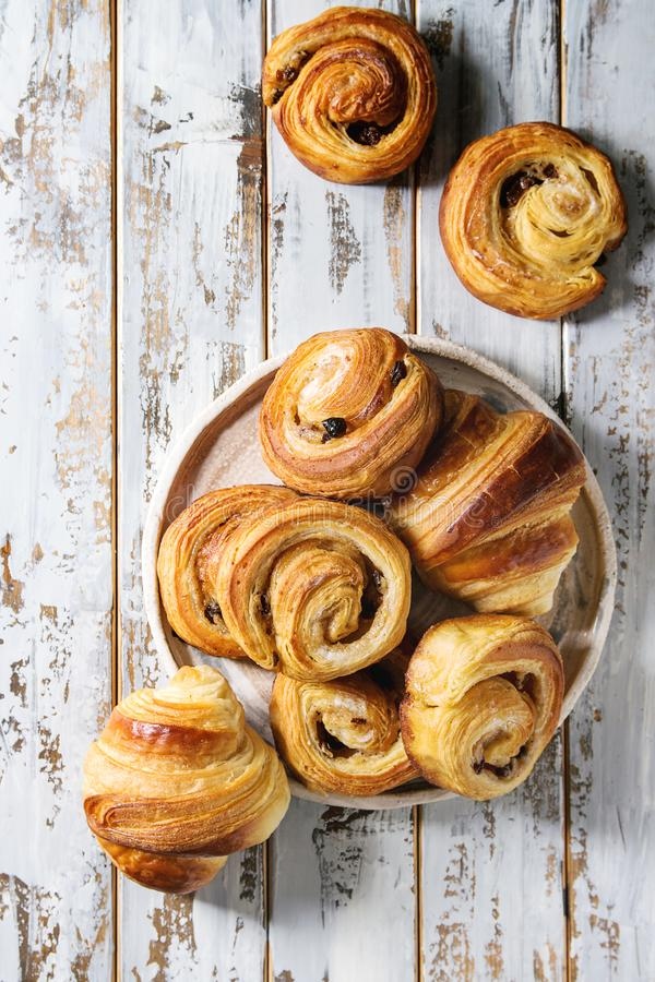 Puff pastry buns. Variety of homemade puff pastry buns cinnamon rolls and croissant in ceramic plate over white plank wooden background. Flat lay, space stock photo
