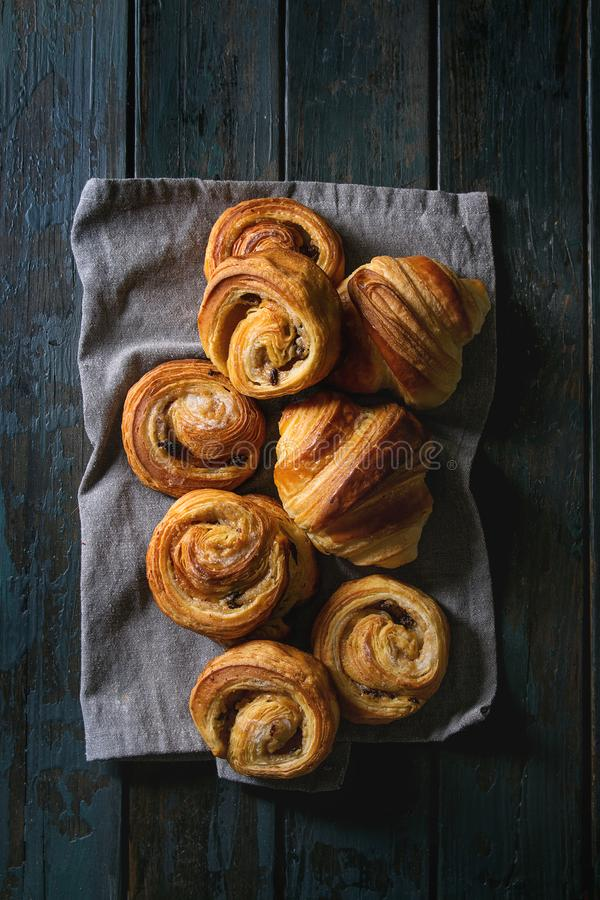 Puff pastry buns. Variety of homemade puff pastry buns cinnamon rolls and croissant on cloth over dark plank wooden background. Flat lay, space royalty free stock images