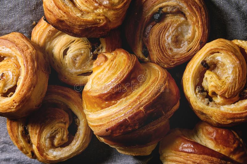 Puff pastry buns. Variety of homemade puff pastry buns cinnamon rolls and croissant over grey cloth. Flat lay, cloth up stock photography