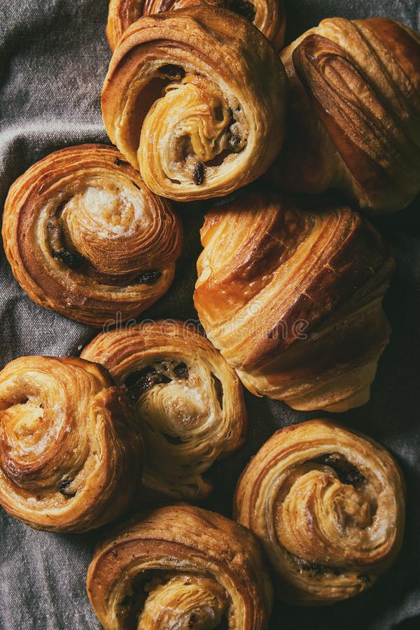 Puff pastry buns. Variety of homemade puff pastry buns cinnamon rolls and croissant over grey cloth. Flat lay, cloth up royalty free stock photo