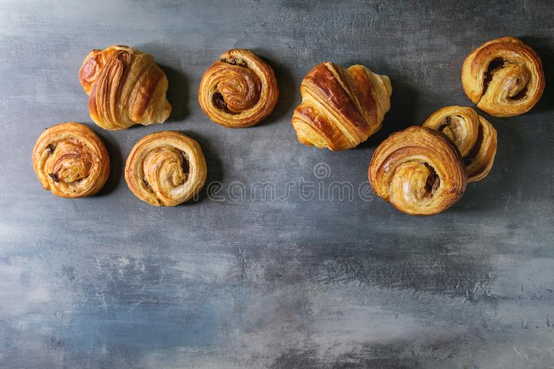 Puff pastry buns. Variety of homemade puff pastry buns cinnamon rolls and croissant in row over blue texture background. Flat lay, space stock image