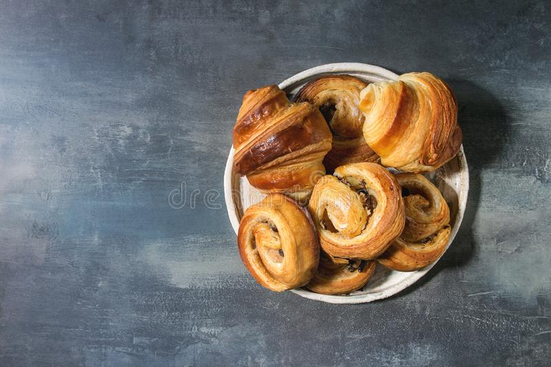 Puff pastry buns. Variety of homemade puff pastry buns cinnamon rolls and croissant served in ceramic plate over blue texture background. Flat lay, space stock photos