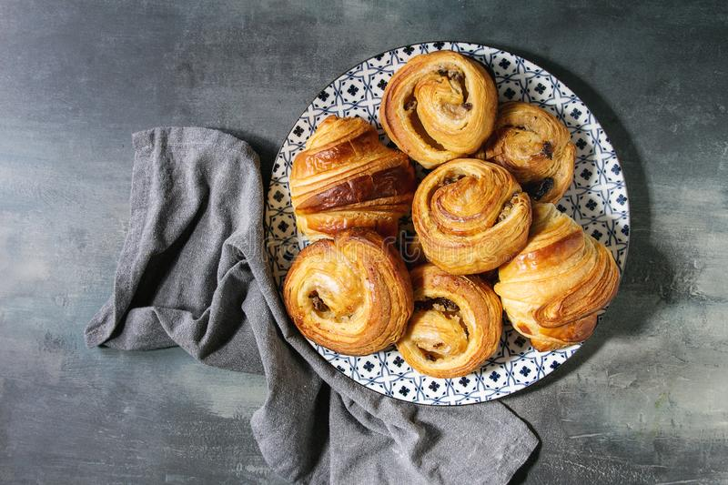 Puff pastry buns. Variety of homemade puff pastry buns cinnamon rolls and croissant served in ceramic plate over blue texture background. Flat lay, space royalty free stock photo