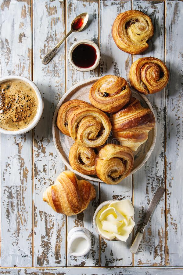 Puff pastry buns. Variety of homemade puff pastry buns cinnamon rolls and croissant served with coffee cup, jam, butter as breakfast over white plank wooden royalty free stock photos