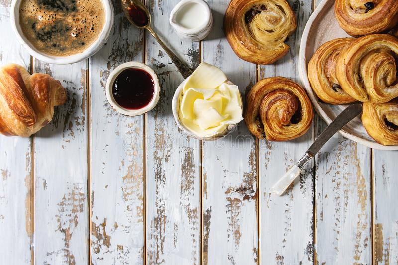 Puff pastry buns. Variety of homemade puff pastry buns cinnamon rolls and croissant served with coffee cup, jam, butter as breakfast over white plank wooden stock photo