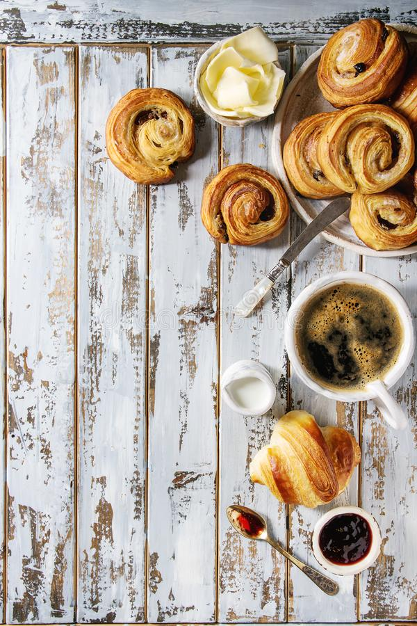 Puff pastry buns. Variety of homemade puff pastry buns cinnamon rolls and croissant served with coffee cup, jam, butter as breakfast over white plank wooden stock photography