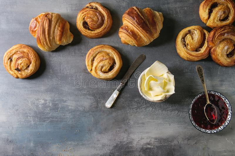 Puff pastry buns. Variety of homemade puff pastry buns cinnamon rolls and croissant served with jam, butter as breakfast over blue texture background. Flat lay stock photography
