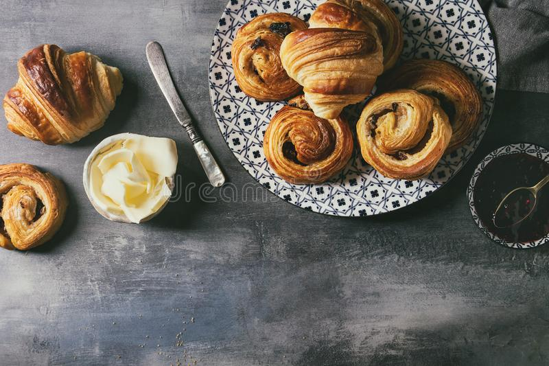 Puff pastry buns. Variety of homemade puff pastry buns cinnamon rolls and croissant served with jam, butter as breakfast over blue texture background. Flat lay stock photos