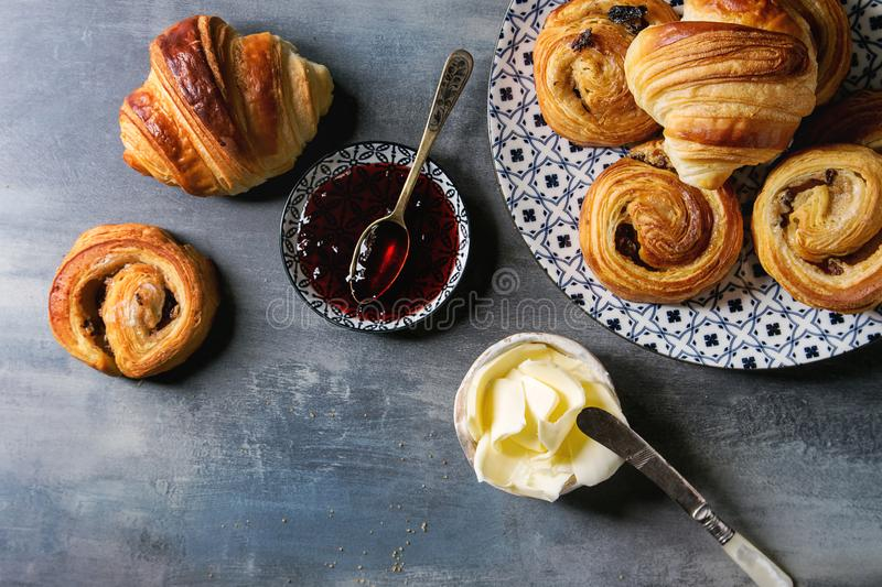 Puff pastry buns. Variety of homemade puff pastry buns cinnamon rolls and croissant served with jam, butter as breakfast over blue texture background. Flat lay royalty free stock images