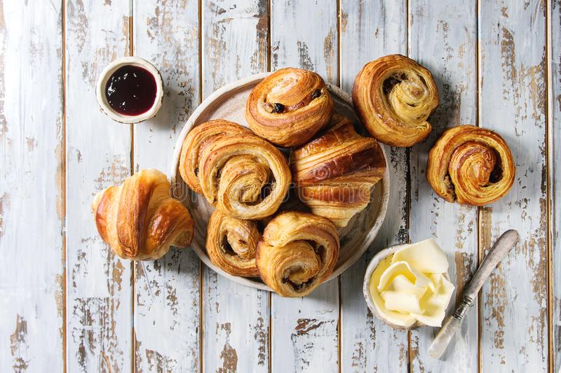 Puff pastry buns. Variety of homemade puff pastry buns cinnamon rolls and croissant served with jam, butter as breakfast over white plank wooden background. Flat stock image