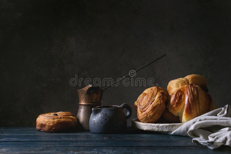 Puff pastry buns. Variety of homemade puff pastry buns cinnamon rolls and croissant served with vintage coffee pot on wooden table. Dark still life. Copy space royalty free stock photography