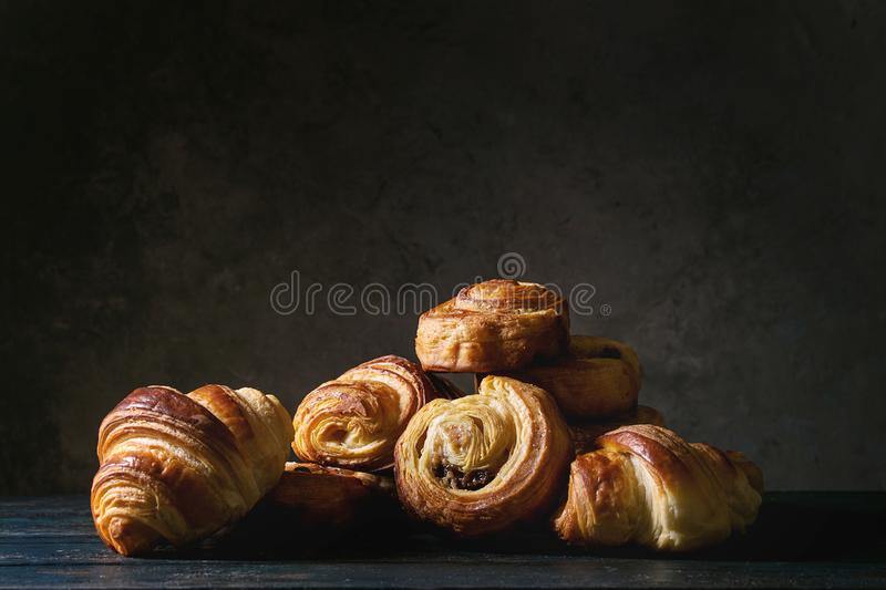 Puff pastry buns. Variety of homemade puff pastry buns cinnamon rolls and croissant on wooden table. Dark still life. Copy space royalty free stock photos