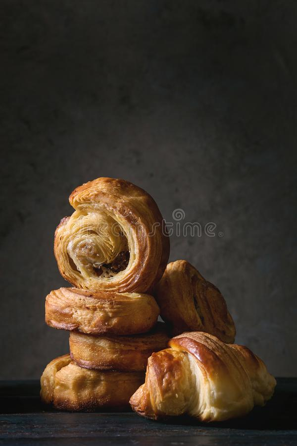 Puff pastry buns. Variety of homemade puff pastry buns cinnamon rolls and croissant on wooden table. Dark still life. Copy space stock images