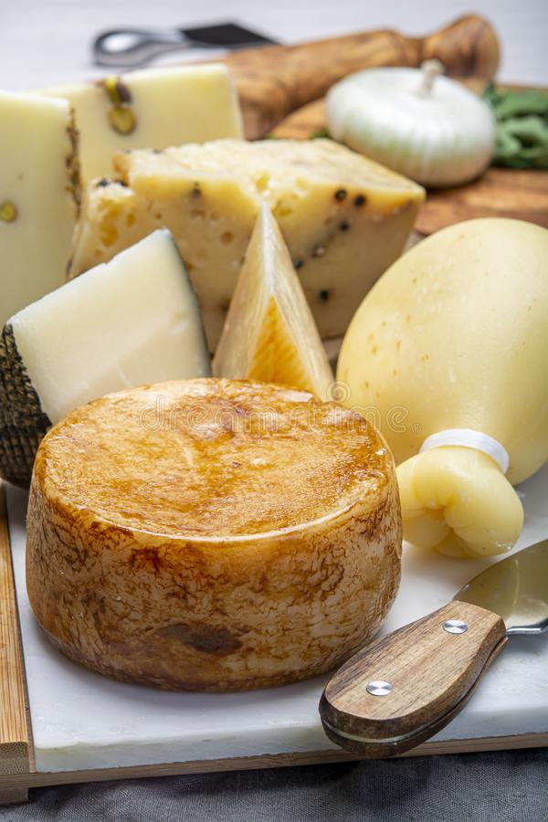 Variety of Italian pecorino and provolone cheeses, yellow aged, with black peppers from Nebrodi, white Il Palio and black royalty free stock photo