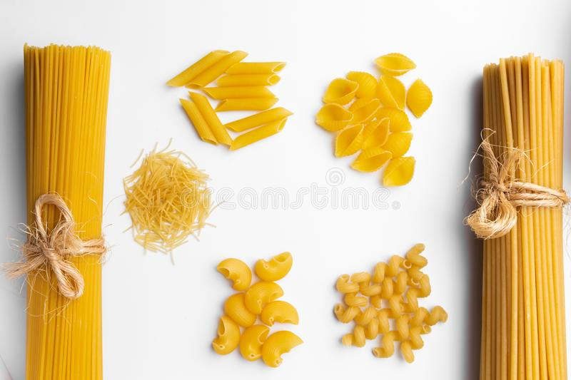 Variety of dry raw italian traditional pasta on white desk royalty free stock images