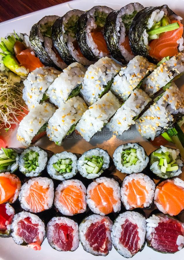 Variety of japanese sushi rolls on a white plate royalty free stock photos