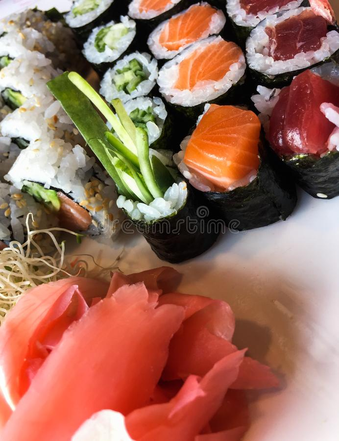 Variety of japanese sushi rolls on a white plate royalty free stock image