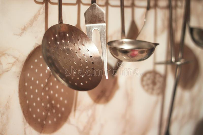 A variety of kitchen utensils are hanging against the background of a marble apron wall stock photos