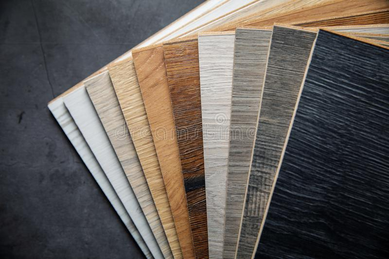 Variety of laminate material samples on dark stone background. Top view stock image