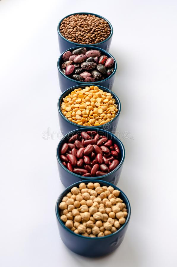 A variety of legumes. Lentils, chickpeas, peas and beans in blue bowls on a white background. Close-up royalty free stock photos