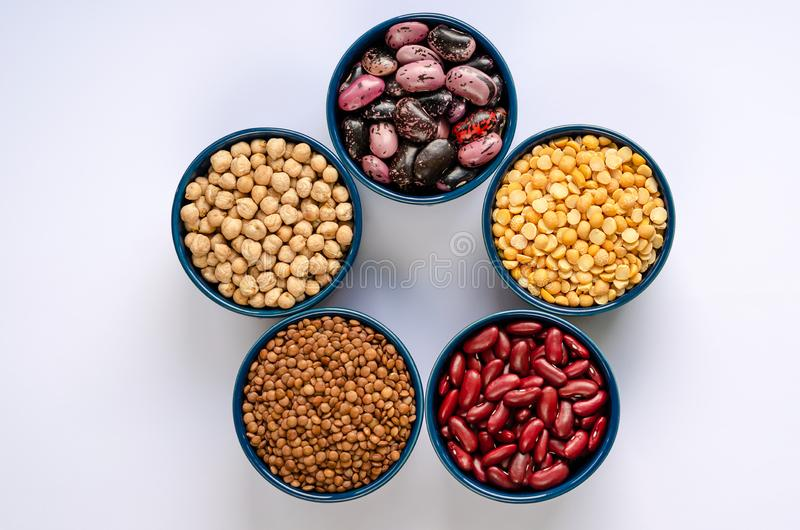 A variety of legumes. Lentils, chickpeas, peas and beans in blue bowls on a white background. Top view stock image
