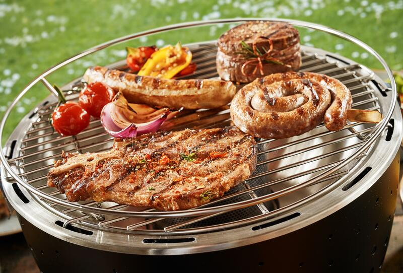 A variety of meat cooking on a gas BBQ royalty free stock photos