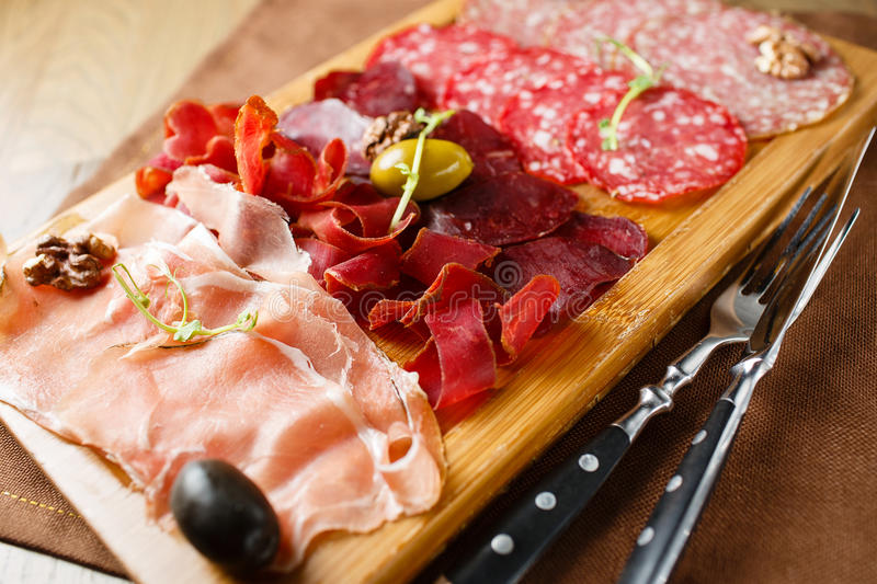 Variety of meats, sausages, salami, ham, olives stock images