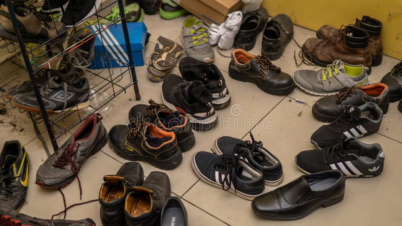 Variety of men`s shoes untidy and disorder in the ground at a men house royalty free stock photos