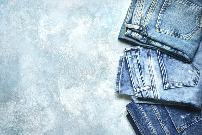 Variety of men and woman blue jeans .Top view with copy space. Variety of men and woman blue jeans on a grunge slate, stone or concrete background.Top view with royalty free stock images
