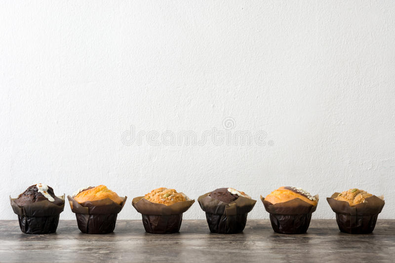 Variety of muffins on a wooden table and white wall stock images