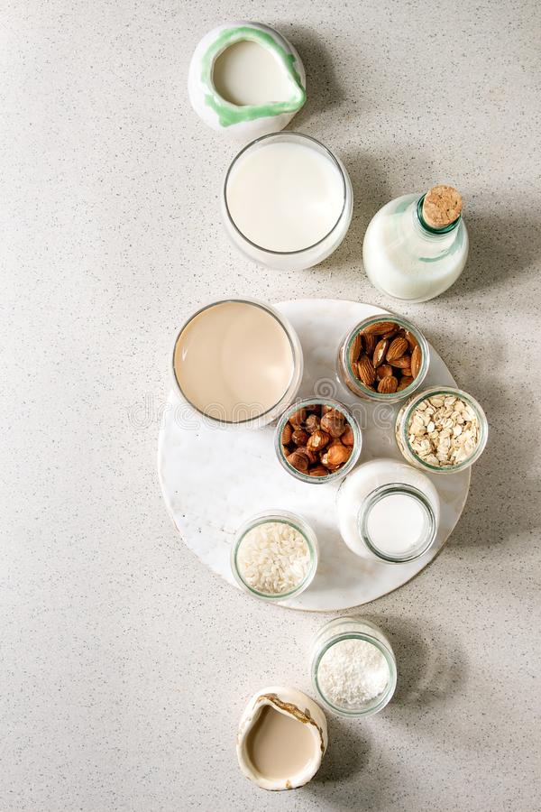 Variety of non-dairy milk. Variety of non-dairy vegan lactose free nuts and grain milk almond, hazelnut, coconut, rice, oat in glass bottles and ceramic jugs royalty free stock images