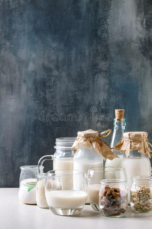 Variety of non-dairy milk. Variety of non-dairy vegan lactose free nuts and grain milk almond, hazelnut, coconut, rice, oat in glass bottles with ingredients stock images