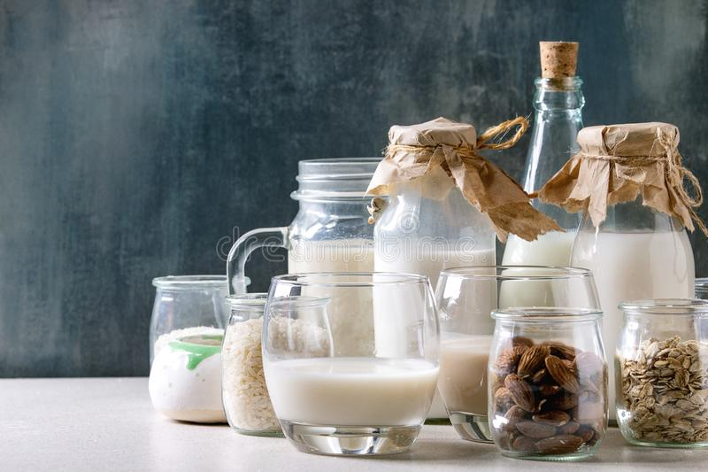 Variety of non-dairy milk. Variety of non-dairy vegan lactose free nuts and grain milk almond, hazelnut, coconut, rice, oat in glass bottles with ingredients royalty free stock photos