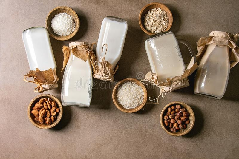 Variety of non-dairy milk. Variety of non-dairy vegan lactose free nuts and grain milk almond, hazelnut, coconut, rice, oat in glass bottles in row with royalty free stock photo
