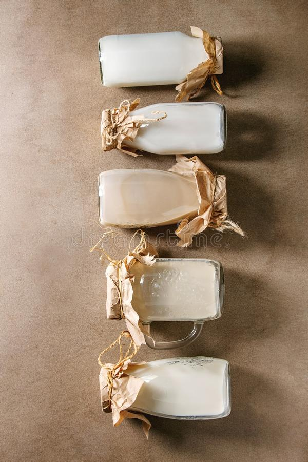 Variety of non-dairy milk. Variety of non-dairy vegan lactose free nuts and grain milk almond, hazelnut, coconut, rice, oat in glass bottles in row over brown stock image