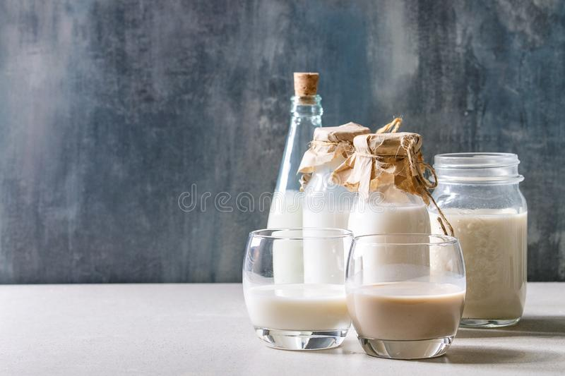 Variety of non-dairy milk. Variety of non-dairy vegan lactose free nuts and grain milk almond, hazelnut, coconut, rice, oat in glass bottles on white table with royalty free stock image