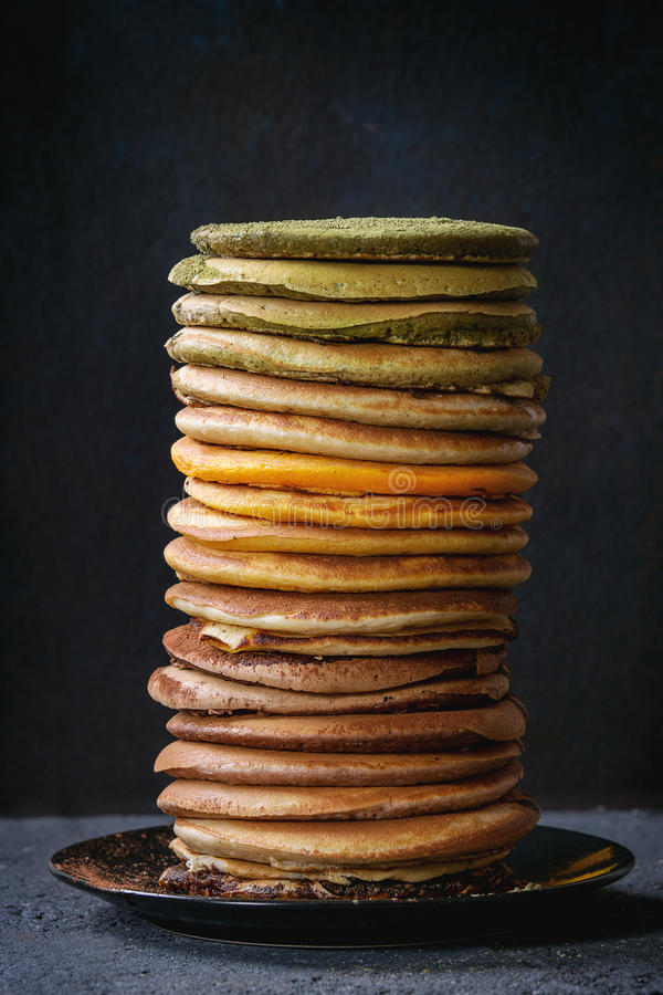 Variety of ombre pancakes. High stack of colorful homemade american ombre chocolate, green tea matcha and turmeric pancakes on plate over black stone texture royalty free stock image